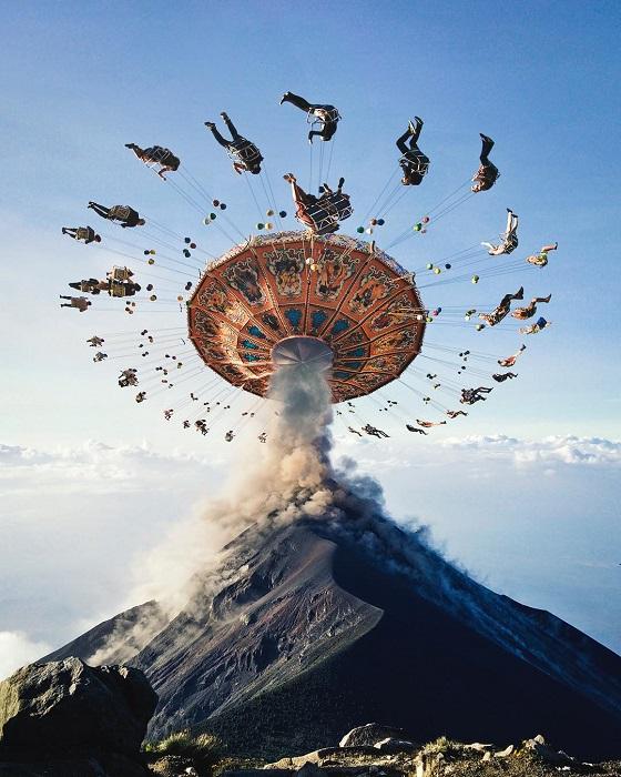 Разноцветная карусель на вершине вулкана, который выпускает клубы дыма.